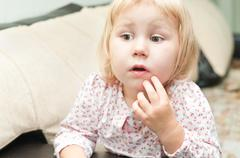 little child a dlond girl sitting on sofa and looking through - stock photo