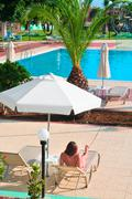 one beautiful woman under parasol is tained near water pool - stock photo