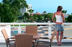 Young beautiful girl standing on the balcony of the hotel and looking into th Stock Photos