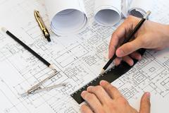 Architect hands drawing project on blueprints by hands - stock photo