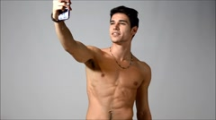 Attractive shirtless young man taking selfie with cell phone - stock footage