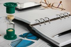 Hourglass, diary, pen, glasses and phone Stock Photos