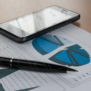 Pen, smartphone  on a background of  chart Stock Photos