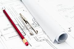 Stock Photo of Pencil and measuring instrument are near construction paper blueprints