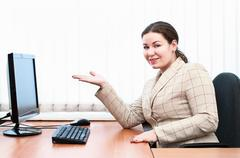 Stock Photo of young caucasian woman point on monitor sitting at the working place. hand fro