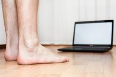 Opened laptop and male feet on the parquet flooring of the room. laptop not i Stock Photos