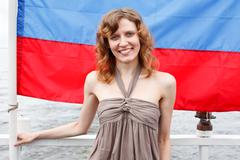 one russian beautiful young female standing under flag of russia - stock photo