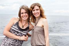 Two young happy women standing together at ship deck, sea cruise, copyspace - stock photo