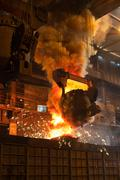 molten metal pouring with sparks from a foundry crucible - stock photo