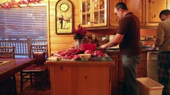 Men cut up slabs of elk meat on a kitchen counter Stock Footage