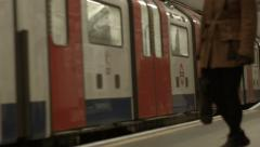 London Underground Tube Train Pulling into station with person waiting Stock Footage