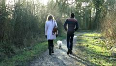 Young couple walking their dog in the woods. - stock footage