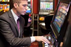 Men gambling in the casino on slot machines Stock Photos