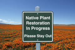 Native plant restoration sign with poppies Stock Photos