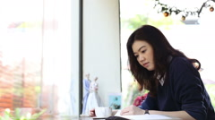Student asian woman drinking coffee and reading a book at coffee shop Stock Footage