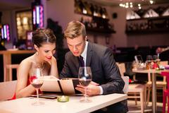 Stock Photo of smiling couple decide what to order