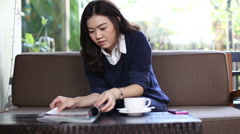 Asian student woman sitting in coffee shop. Reading a book Stock Footage