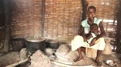 Africa village young woman breast feeding baby Guinea Bisseau Stock Footage