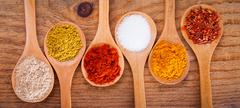Assortment of powder spices on spoons on wooden background Stock Photos