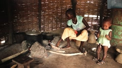 Africa village young woman cooking and baby Guine Bissau Stock Footage