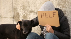 Homless holding help sign and petting his dog Stock Footage