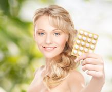 Stock Photo of happy young woman holding package of pills