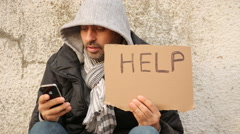 Homless with iPhone, Young man sitting on the street seeking for financial help Stock Footage