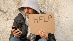 Homeless with help sign using smartphone Stock Footage