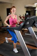 young man running at treadmill in gym - stock photo