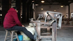 Woman working on a traditional manual silk reeling machine Stock Footage