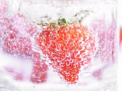 Strawberry in mineral water with boobles Stock Photos