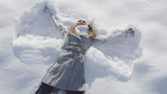 SLOW MOTION: Woman jumps into snow and makes an angel - stock footage