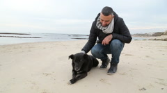 Man petting his dog on the beach - stock footage