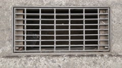 Storm drain in road Stock Footage