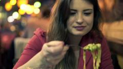 Young beautiful woman eating pasta in restaurant at ngiht HD Stock Footage