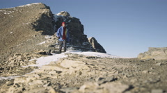 A man walking along a ridgeline at the summit of a mountain Stock Footage
