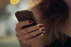 Close up of woman hands texting, sending sms on smartphone at night in city NTSC Stock Footage