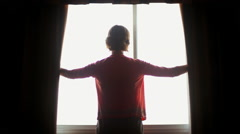 Young woman spreading curtains open to reveal light Stock Footage