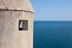 Gun turret on old city walls of dubrovnik (croatia) with adriatic sea in back Stock Photos