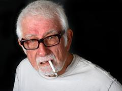 Elderly man smoking a cigarette with an angry look on his face Kuvituskuvat