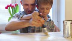 Father with Little son painting  table in white Stock Footage