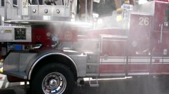 Firemen Stand on Truck as Water Pumps Stock Footage
