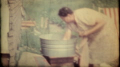 1600 - washing clothes in wash tub by hand - vintage film home movie - stock footage