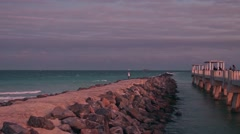 Fisherman catches fish on rock jetty at South Point South Beach in Miami Florida Stock Footage