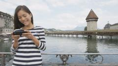 Woman using smartphone app in Lucerne Switzerland Stock Footage