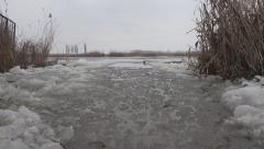 Unfrozen, melted spot on the icy surface of the river with reeds Stock Footage