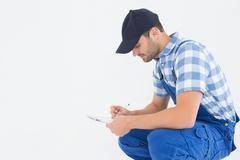 Handyman crouching while writing on clipboard Stock Photos