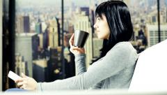 Young woman relaxing watching television drinking coffee at home in New York. Stock Footage