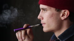 Profile Young Man in Cap Vapes Smokes an E-Cigarette Stock Footage