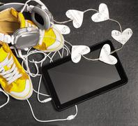 love for music concept. yellow sneakers, headphones, tablet,hearts. - stock photo